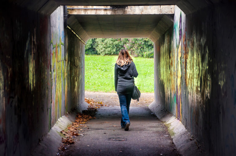 woman walking alone through a tunnel